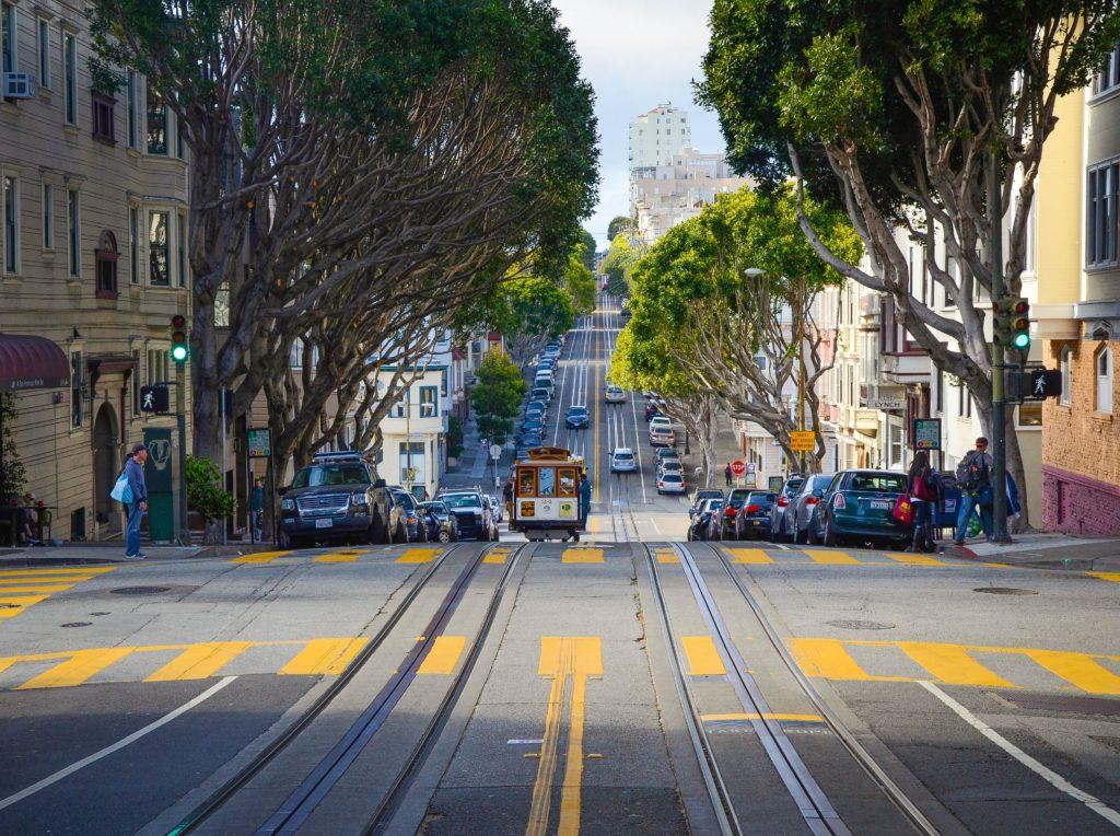 Foto de rua ampla em San Francisco, nos EUA, com trilho de bondinho no centro