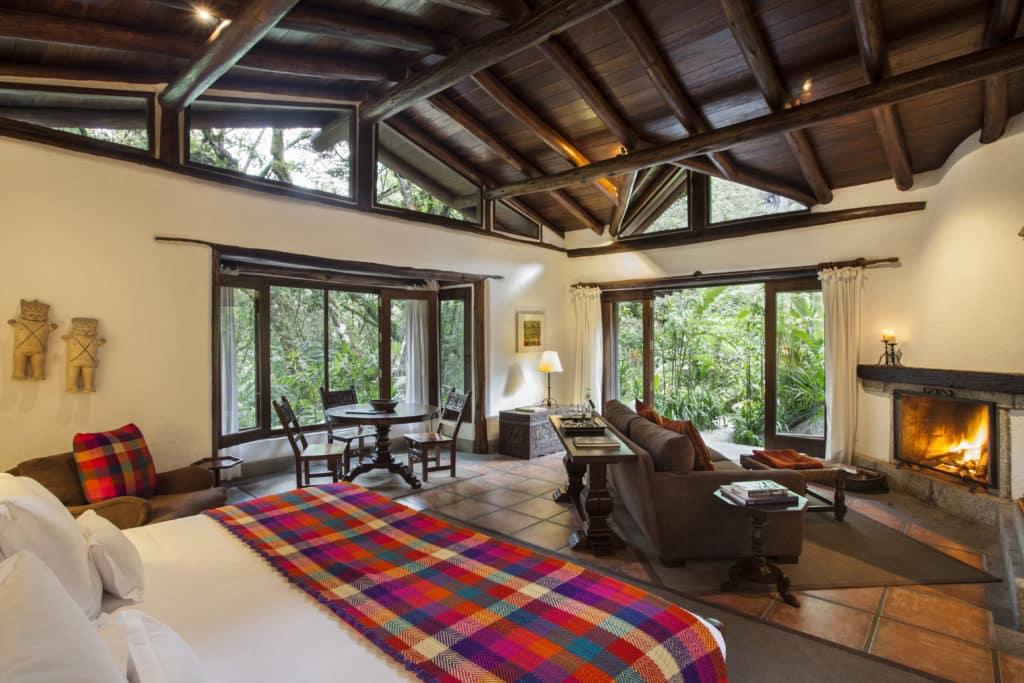 Foto de amplo espaço de suíte do Inkaterra, um dos hotéis de luxo em Machu Picchu, com vista para floresta e lareira no quarto