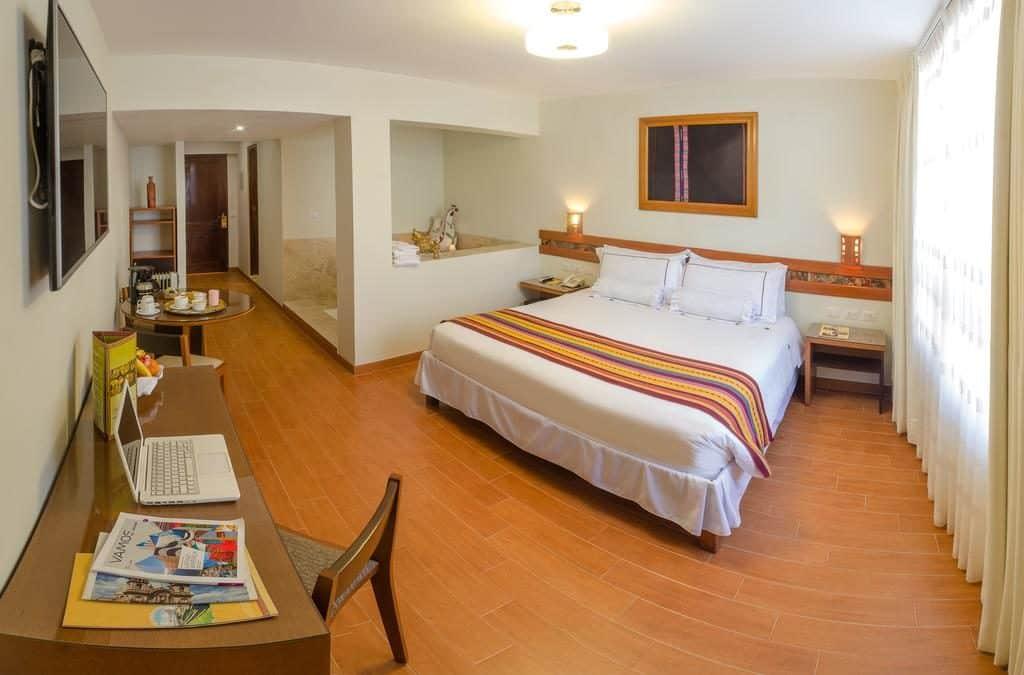 Foto ampla de quarto no Taypikala Hotel Cusco, com escrivaninha e cama grande