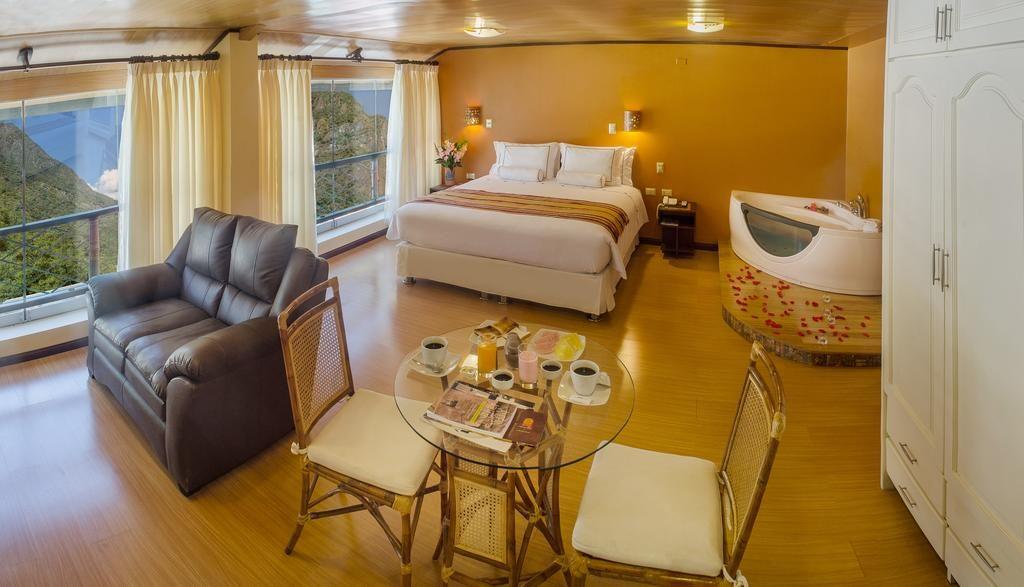Suíte completa com cama de casal, sofá, mesa para café da manhã, armário, banheira de hidromassagem no Taypikala Machu Picchu