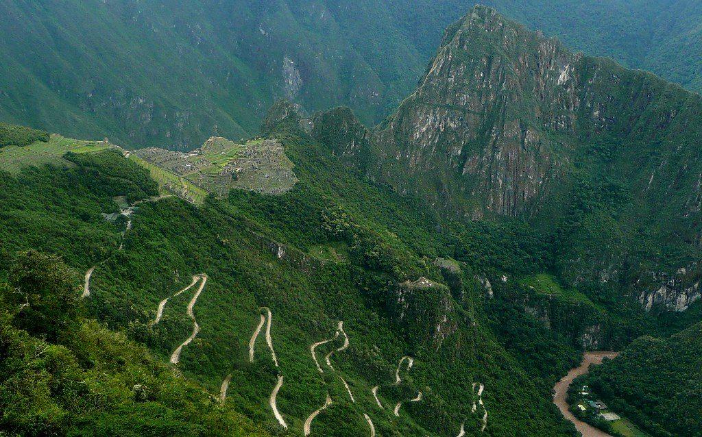 Vista de caminhos e ruínas ao fundo que se tem ao chegar em Machu Picchu pela trilha inca