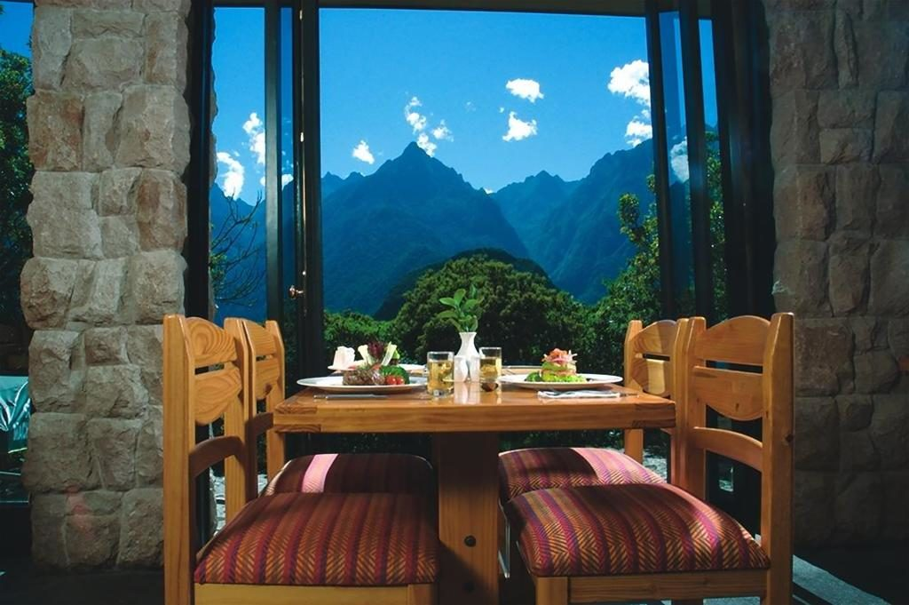 Foto de mesa do restaurante do hotel em Machu Picchu, Belmond Sanctuary Lodge, com vista para as montanhas ao redor