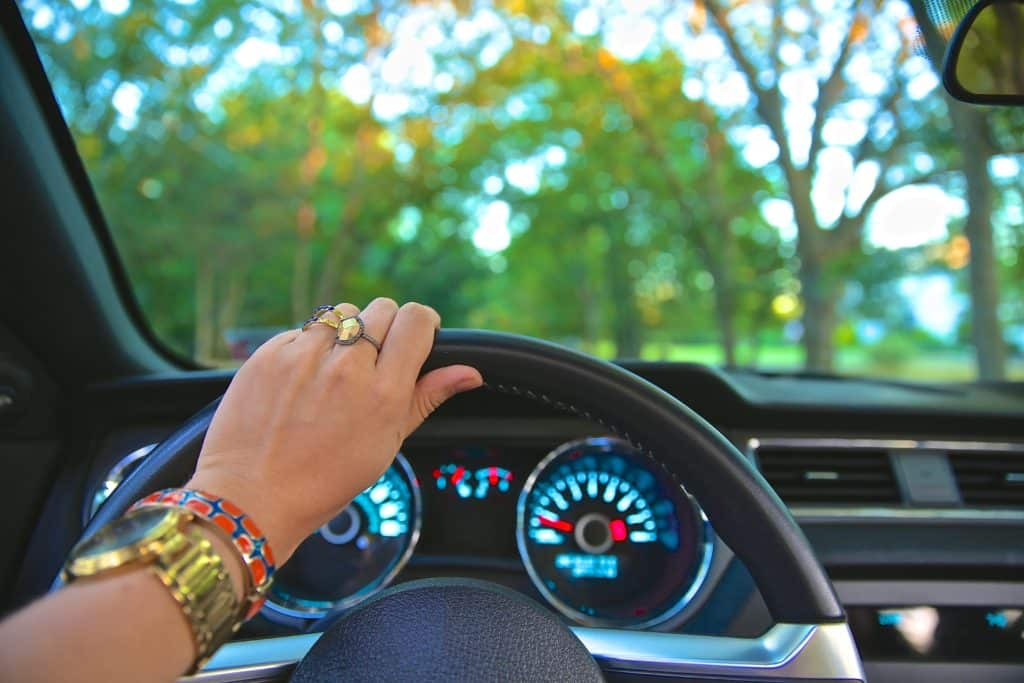 Mão de mulher em volante - aluguel de carro em Portugal