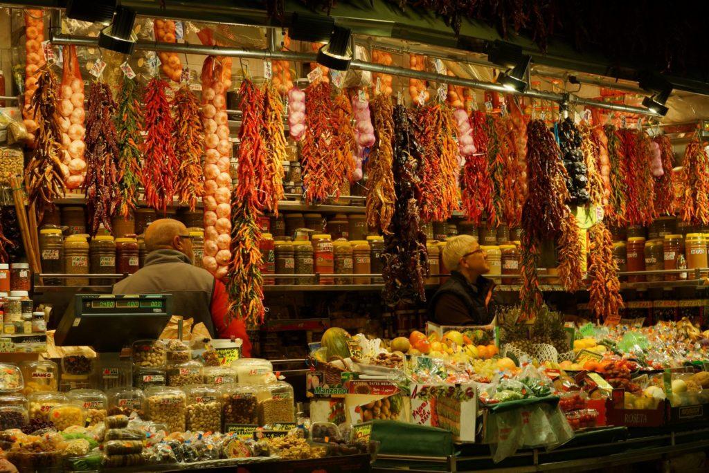 Foto de temperos a venda em mercado de Barcelona, com alho, pimentas, entre outras iguarias