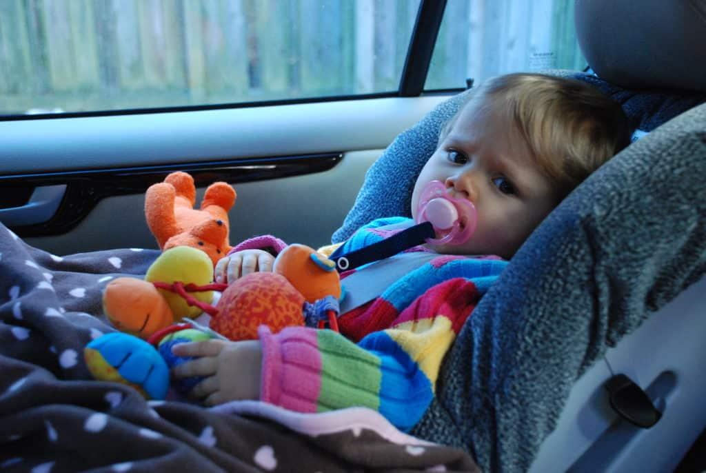 Foto de criança com roupinha colorida e brinquedo nas mãos, ajeitada na cadeirinha, para o post aluguel de carros Salvador
