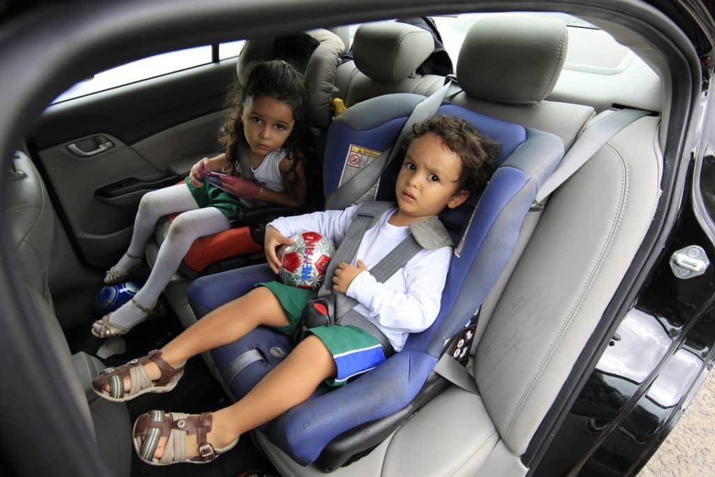 Menina e menino sentados em cadeirinhas no banco de trás do carro