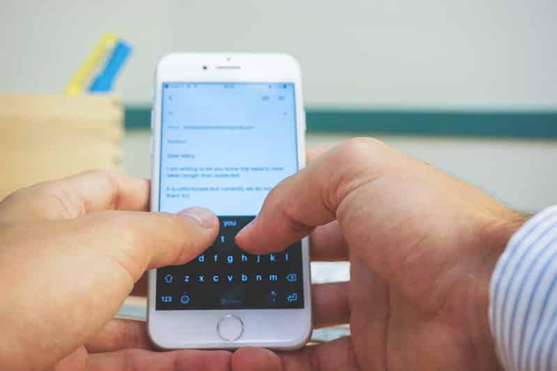 Foto de pessoa segurando celular com as mãos e digitando
