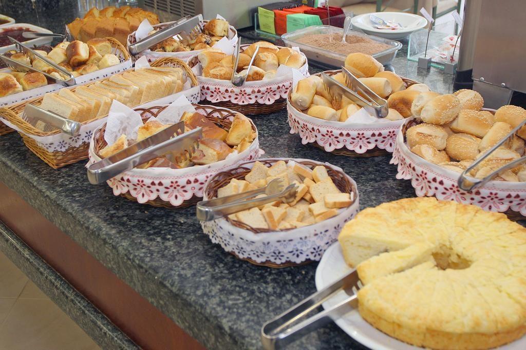 Mesa de café da manhã com várias opções de pães e bolos no hotel