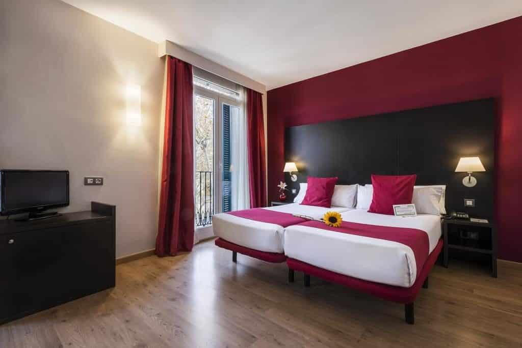 Foto de quarto colorido com girassol na cama para os hóspedes, no Hotel Oriente em Barcelona