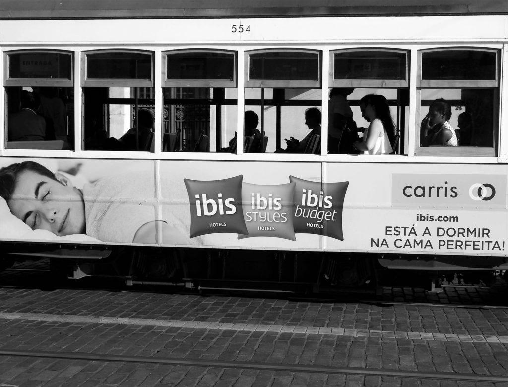Foto em preto de branco de propaganda dos hotéis Ibis em Lisboa, em meio de transporte da cidade