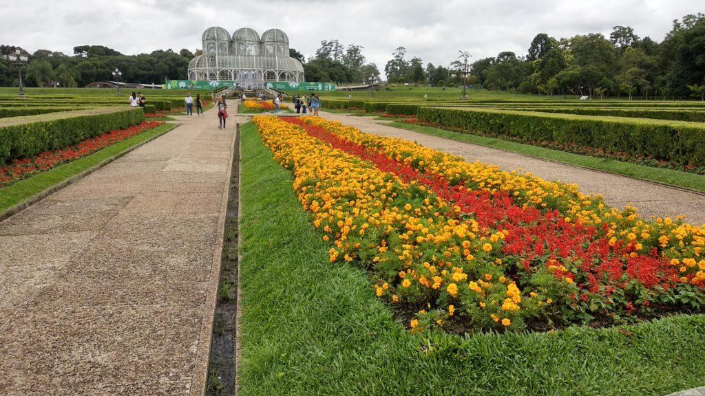 Foto do Jardim Botânico de Curitiba, com canteiro de flores e arbustos dos jardins franceses, além da estufa que é símbolo do local e da cidade.