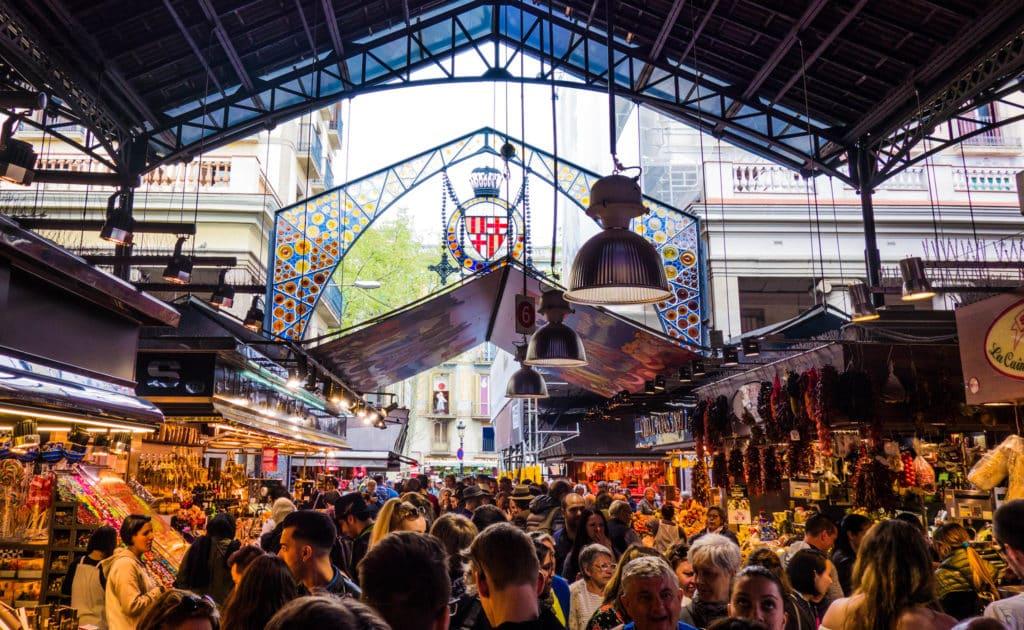 Entrada do La Boqueria vista de dentro do mercado, cheio de pessoas caminhando entre os stands. Foto de G0DeX via Flickr