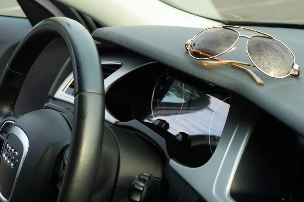 Foto de painel de carro com óculos de sol apoiado ilustrando post de aluguel de carro em Fortaleza