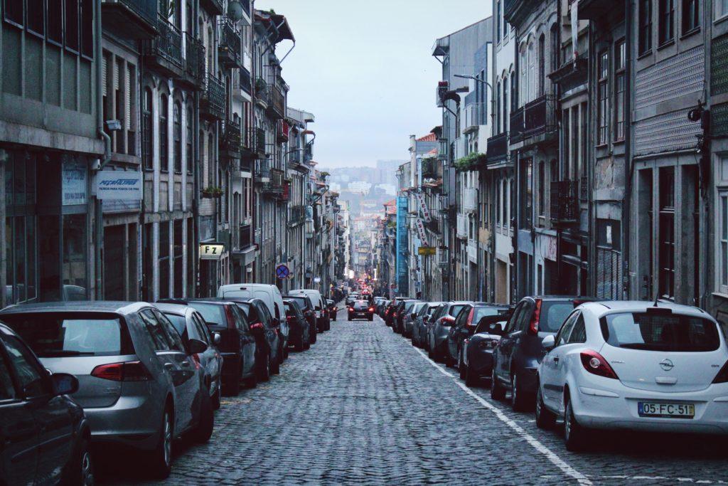 Rua do centro de Porto, em Portugal, tomada por carros estacionados.