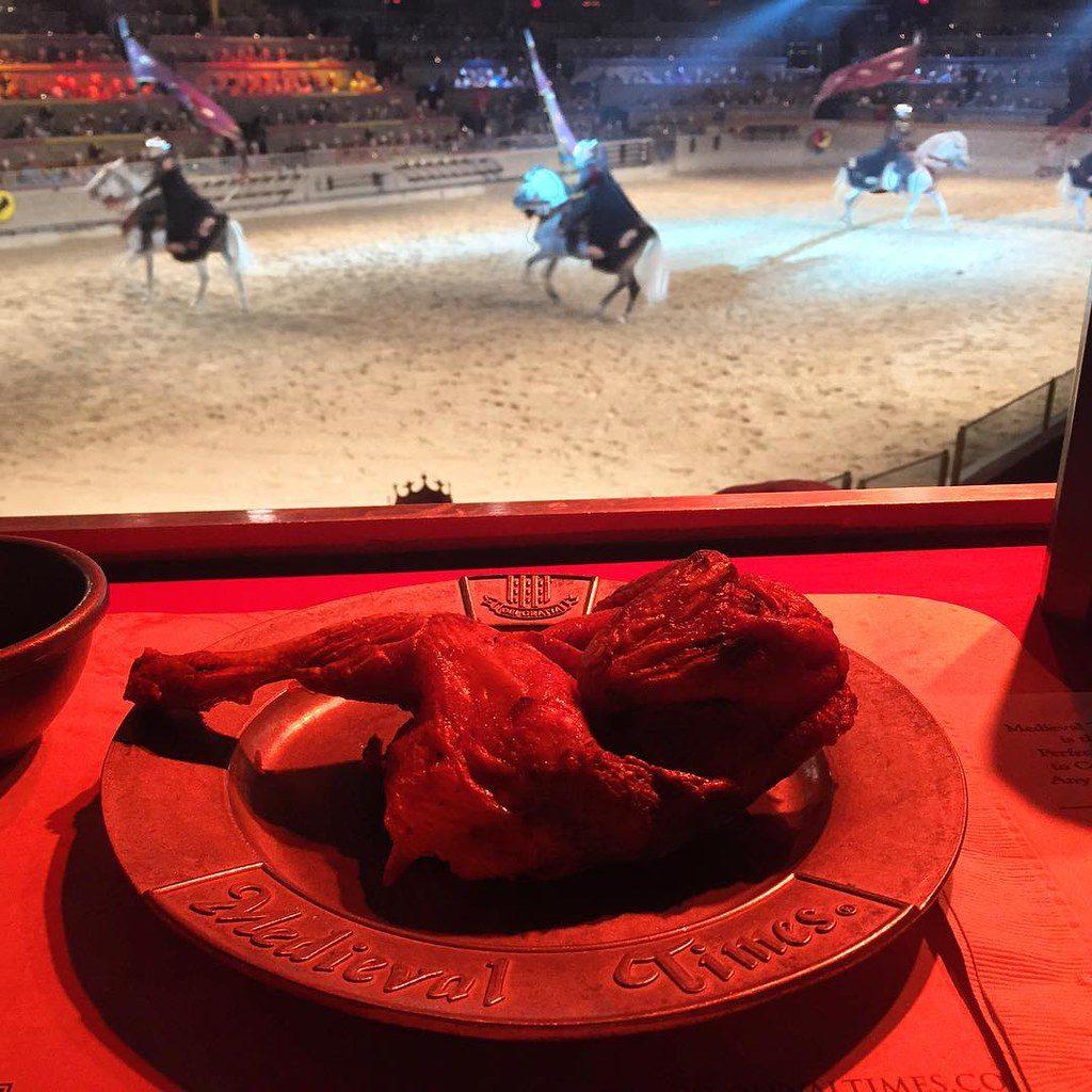 Foto de prato de carne em primeiro plano, com apresentação de pessoas em armaduras medievais montando cavalos, para ilustrar post de Anaheim em sessão sobre onde comer