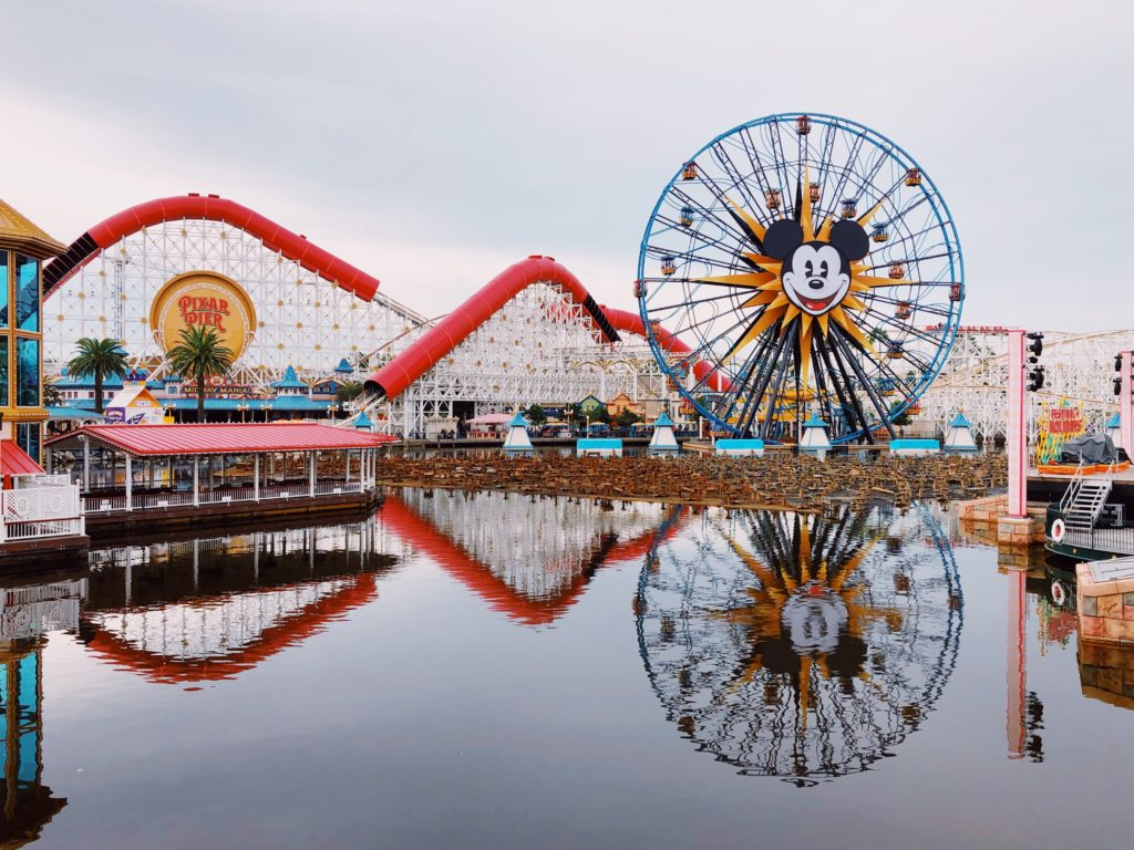 Imagem do Pixar Pier, cartão postal do Disney California Adventure, com lago espelhando a roda gigante do Mickey