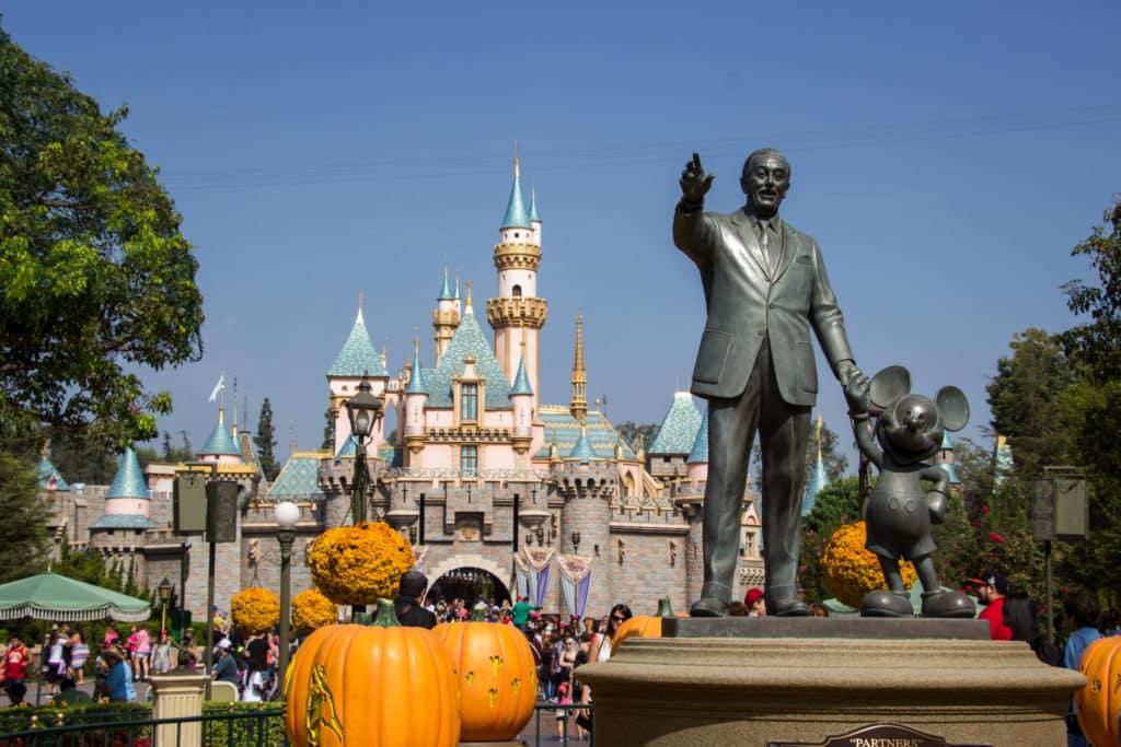 Estátua de Walt Disney com Mickey e castelo da Disney Califórnia ao fundo, em época de Halloween