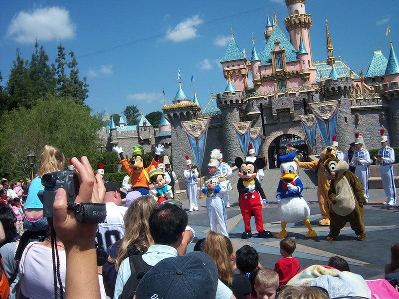 Pateta, Pinóquio, Mickey, Pato Donald, Pluto e Tico dançando com banda de fanfarra em frente ao castelo da Bela Adormecida