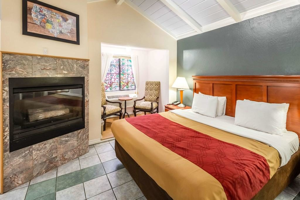 Foto de quarto aconchegante com lareira e cama ampla no Econo Lodge Inn