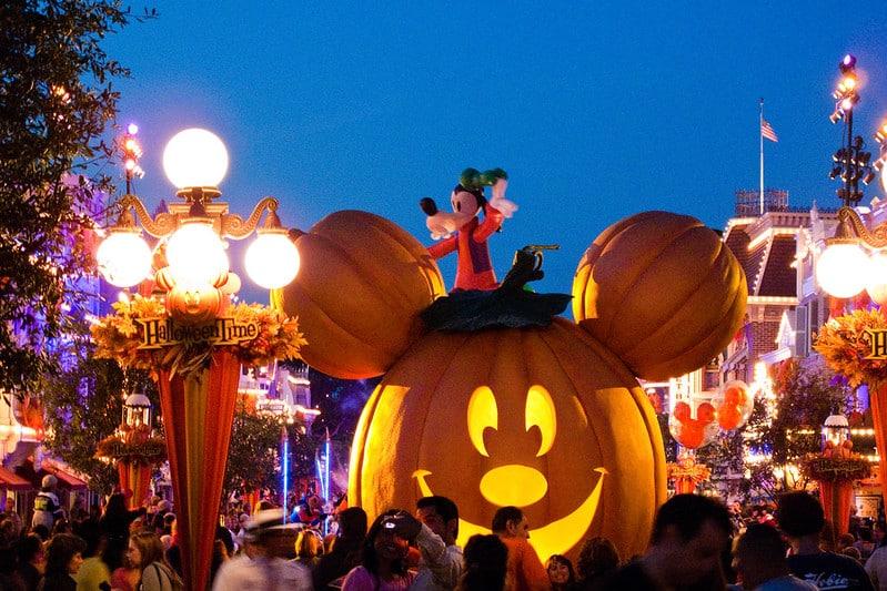 Foto de decoração de Halloween no Disneyland Park, com abóbora gigante com a cara do Mickey e Pateta sobre ela, acenando