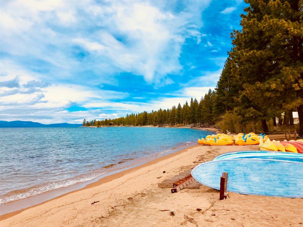 Foto de praia do Lake Tahoe durante o verão, com árvores verdinhas
