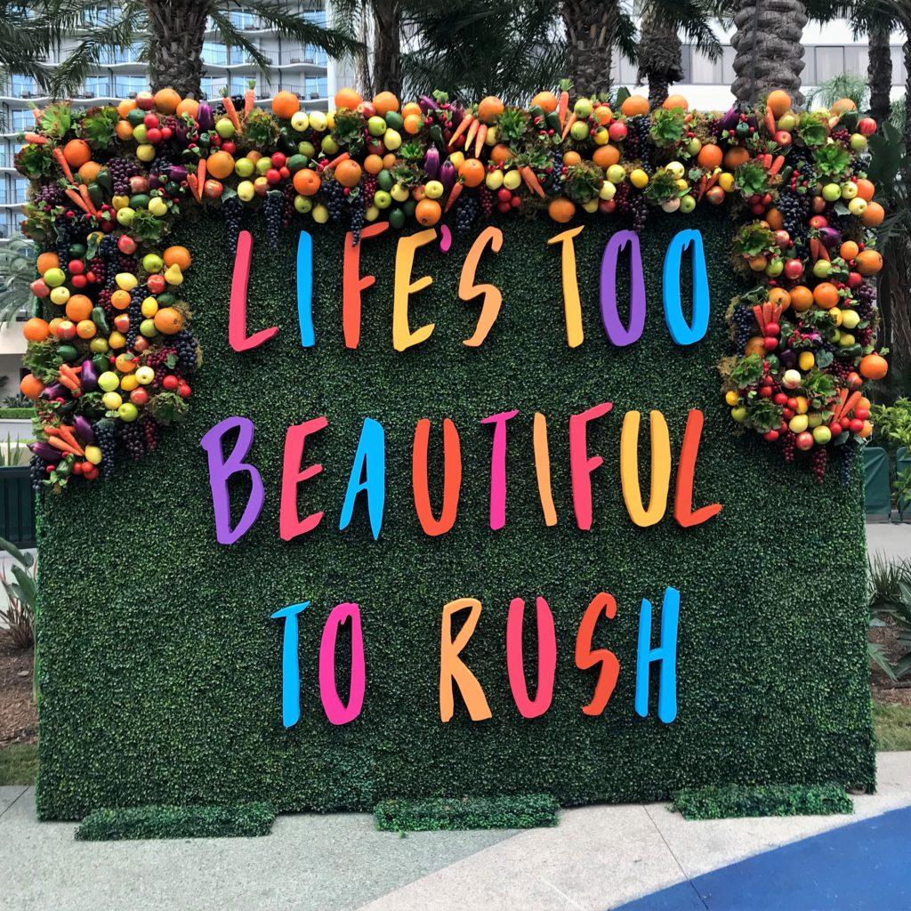 """Painel colorido com frutas, grama sintética e letras estilizadas com os dizeres """"life's too beautiful to rush"""""""