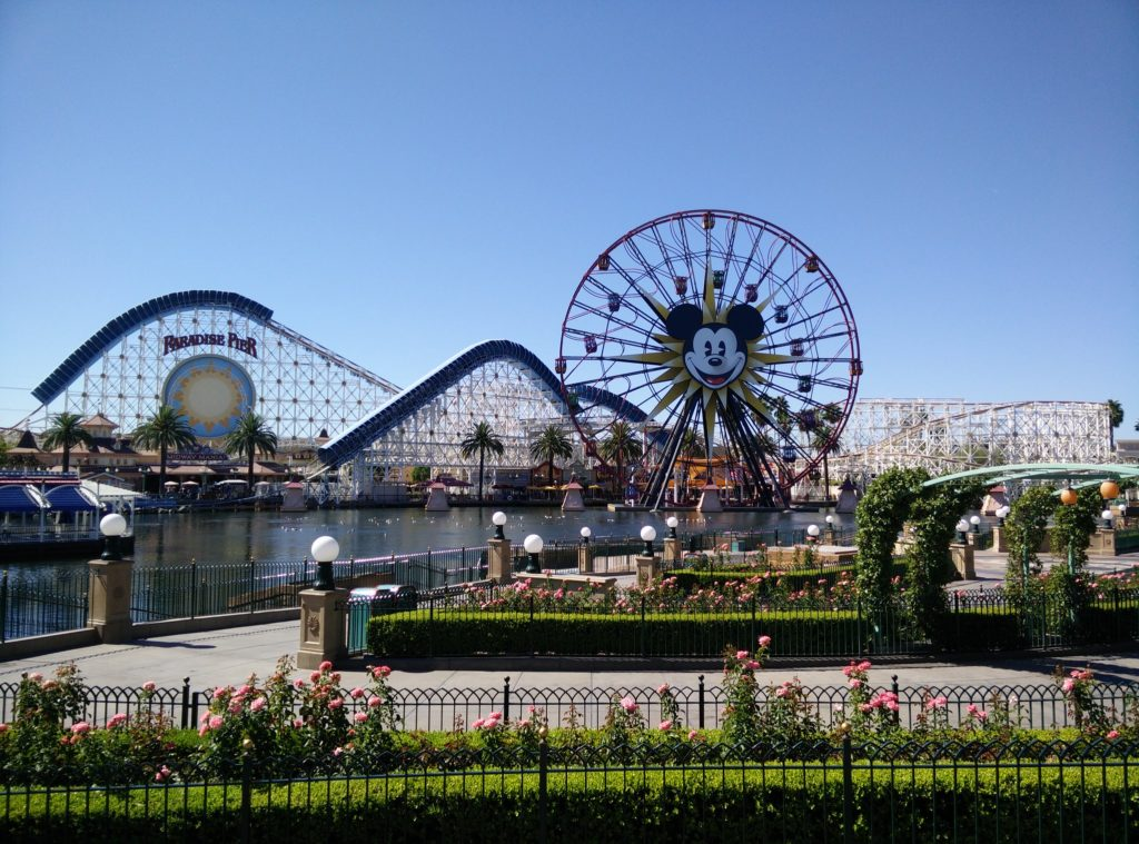 Parte do Disneyland Park em Anaheim, com montanha russa com o rosto do Mickey, lago e canteiros com jardins floridos