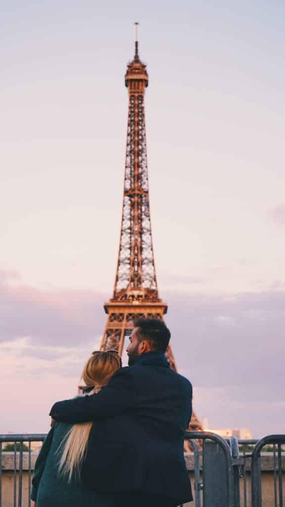 Casal em lua de mel em Paris em frente a Torre Eiffel.