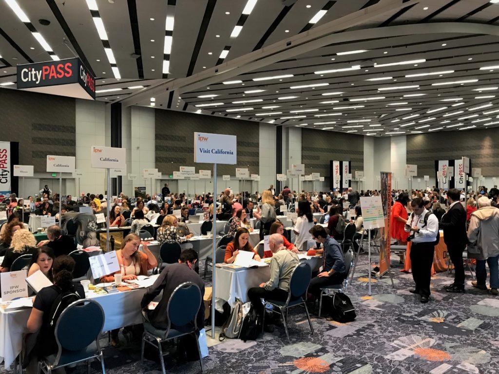 Foto de parte interna do Anaheim Convention Center durante o IPW 2019, com várias pessoas em meetings nas mesas do evento