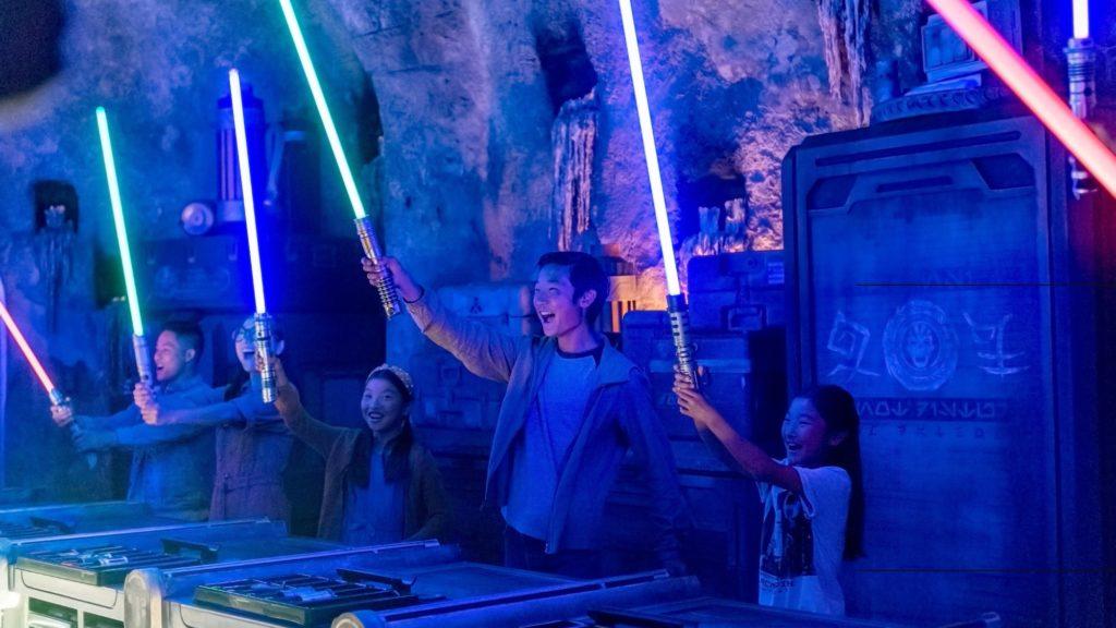 Foto oficial do site da Disney mostrando pessoas com sabre de luz ao participar de experiência no Savi's Workshop