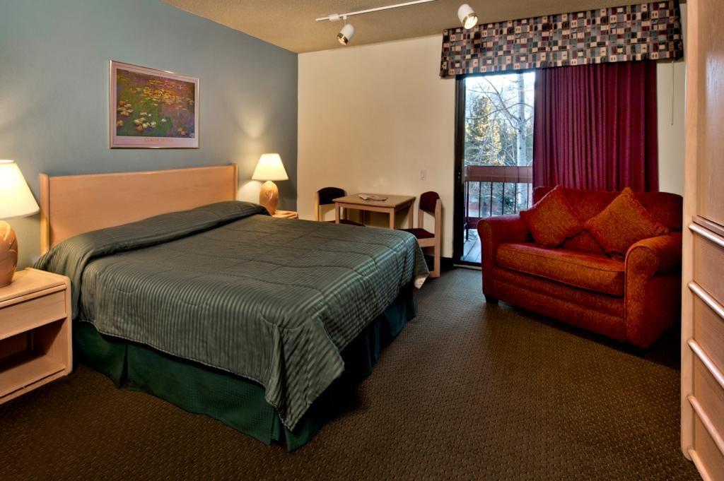 Quarto do hotel Sierra Lodge, em Mammoth Lakes, com cama de casal, poltrona grande, armário, abajures e cortina