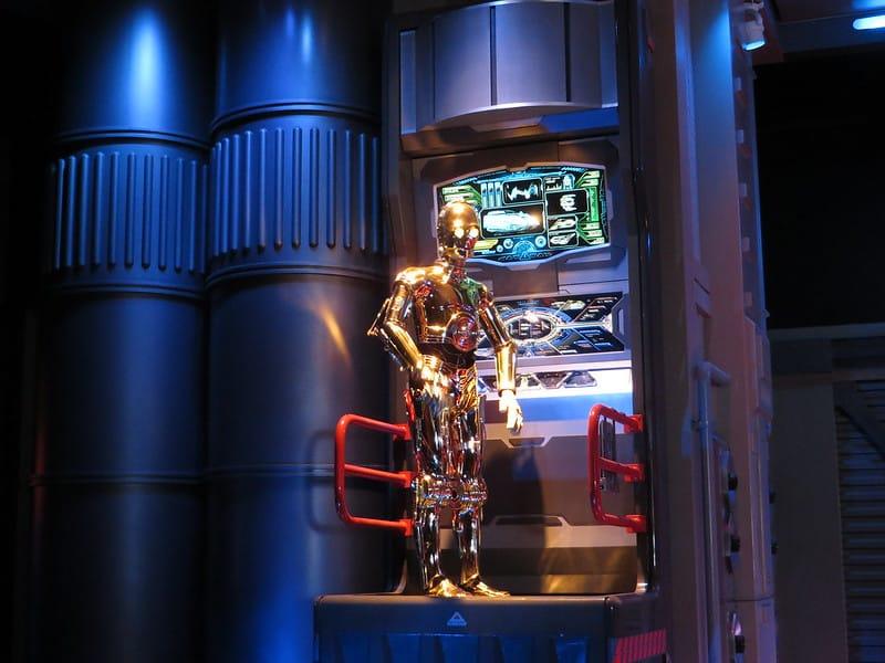 C-3PO parado sobre plataforma em cenário de Star Wars, em atração temática da Disney California