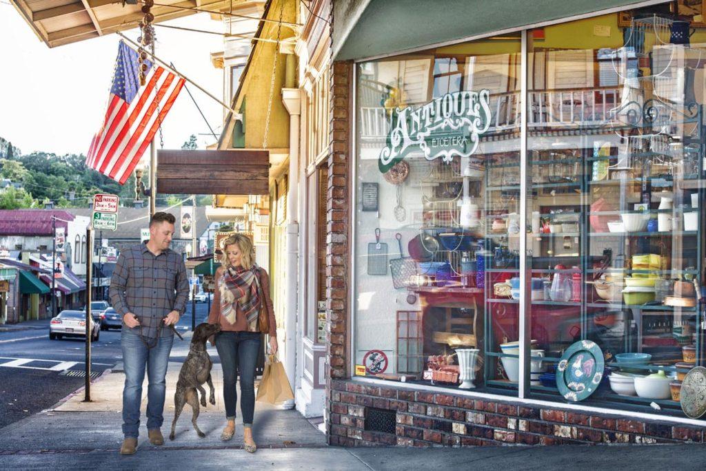 Casal com cachorro em frente a loja de antiguidades no centro de Sonora, principal cidade do condado de Tuolumne