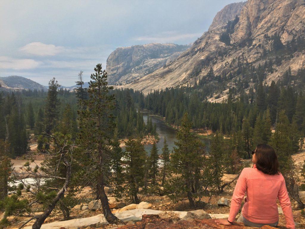 Colunista Cau Pelegrini sentada em mirante com vista para lago e árvores coníferas, no Yosemite