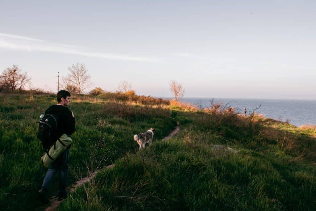 Pessoa viajando a pé com cachorro em local com bastante vegetação rasteira e mar ao fundo