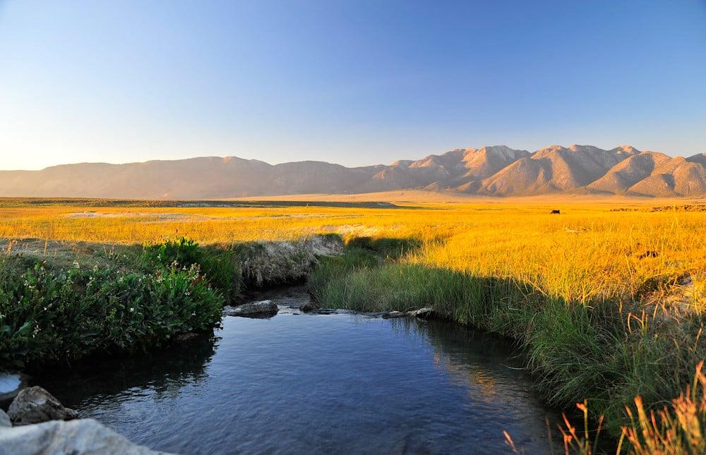 Foto com vista de piscina termal Wild Willy's Hot Spring e paisagem ao fundo