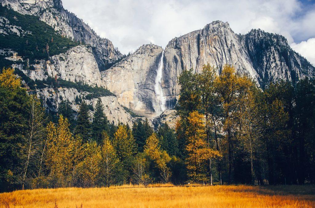 Vista de paisagem do Parque Nacional de Yosemite no outono, com árvores de folhas amareladas a cachoeira ao fundo