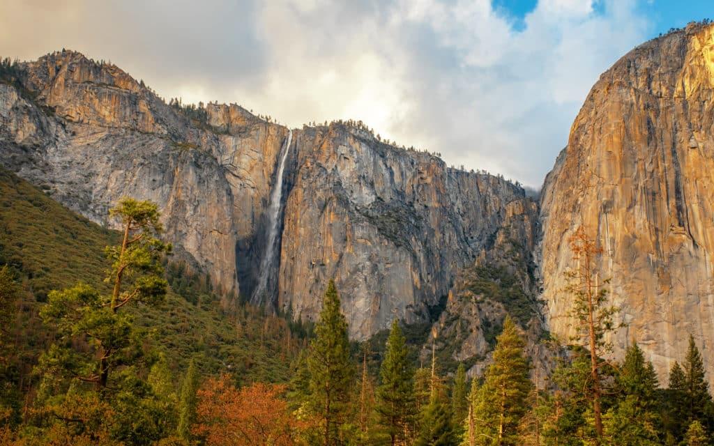 Paisagem de primavera no Yosemite National Park, com cachoeira ao fundo e árvores na frente das rochas