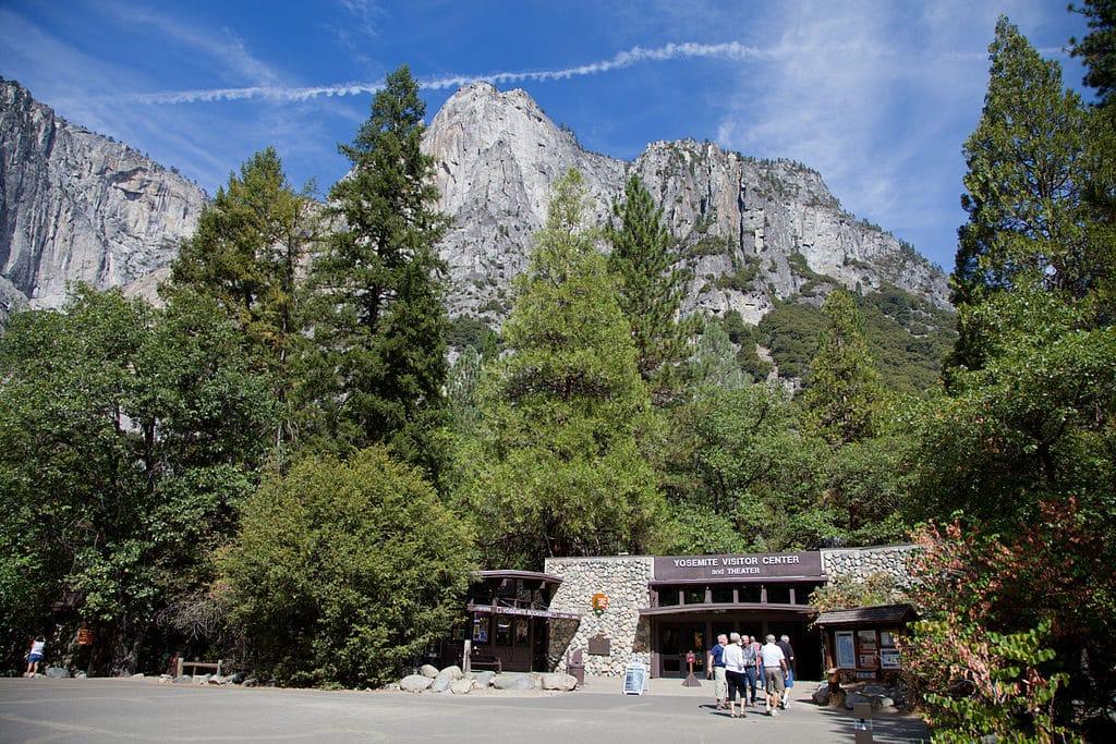 Foto do centro de visitantes do parque, com árvores ao redor e pessoas entrando