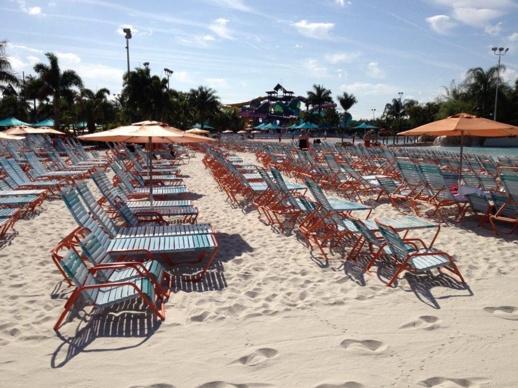 Foto de praia artificial do Arquatica Orlando com guarda-sol, cadeiras e espreguiçadeiras em chão de areia