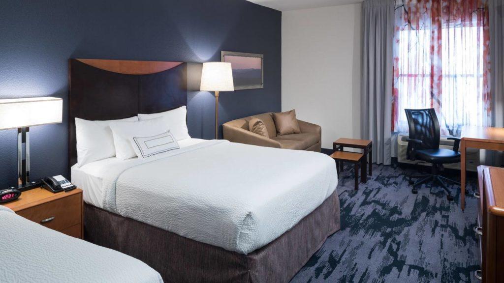 Foto de quarto espaçoso no Fairfield Inn, com duas camas de casal, sofá, carpete, cortinas e mesinhas.