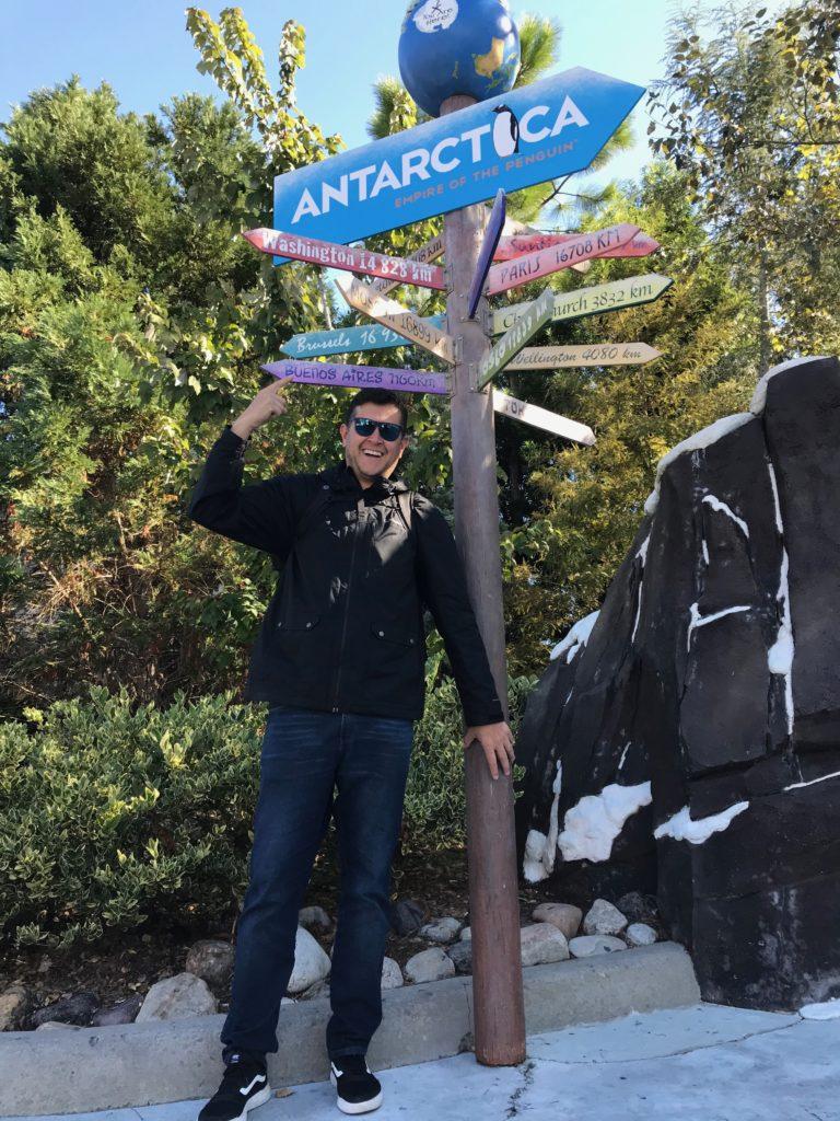 Flávio Antunes próximo à placa indicativa de diferentes pontos ao redor do mundo