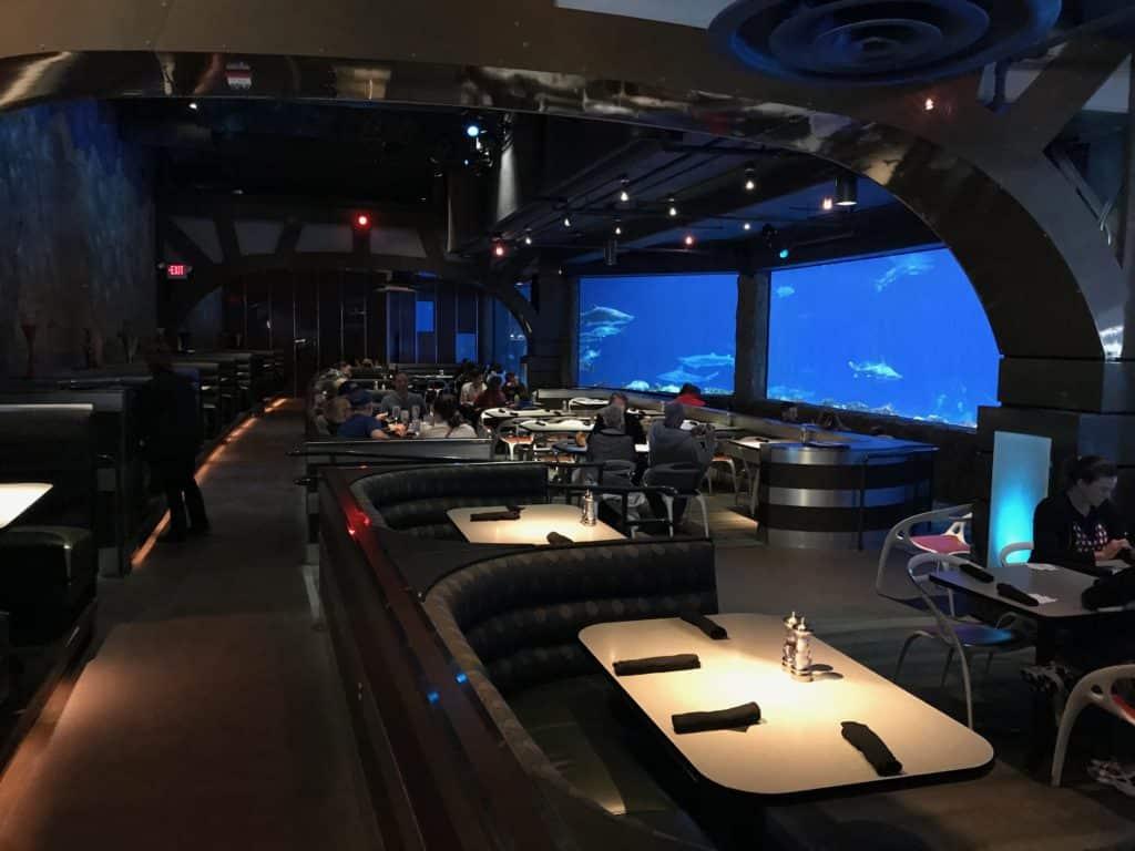 Espaço do restaurante Sharks Underwater Grill, com mesas, lugares vagos para clientes, e uma parede toda ocupada por um aquário com tubarões