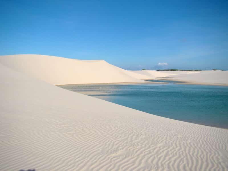 Foto em área com dunas de areia fina e branca e lagos naturais no caminho entre Barreirinhas, Atins e Caburé, na Rota das Emoções