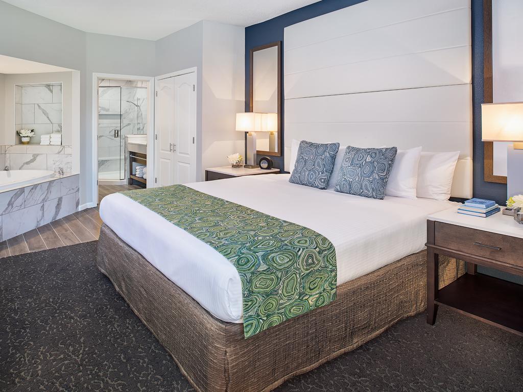 Foto de quarto aconchegante com banheira e cama de casal no Caribe Royale Orlando