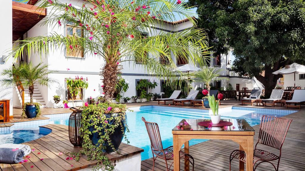 Foto de área comum da pousada Casa de Santo Antônio, com piscina, mesa com cadeiras e espreguiçadeiras