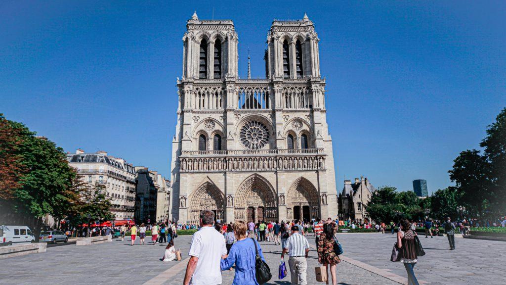 Foto da Catedral de Notre-Dame, um dos pontos turísticos de Paris, antes do incêndio que a interditou, em dia de grande fluxo de pessoas e céu azul sem nuvens
