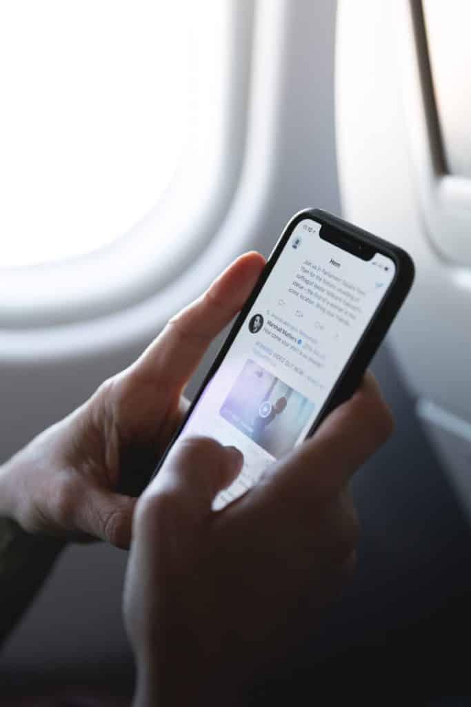 pessoa segurando celular dentro da cabine de avião representando consumidores da marca america chip