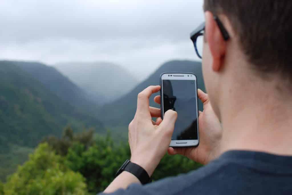 homem mexendo no celular em meio as montanhas de um dia nublado