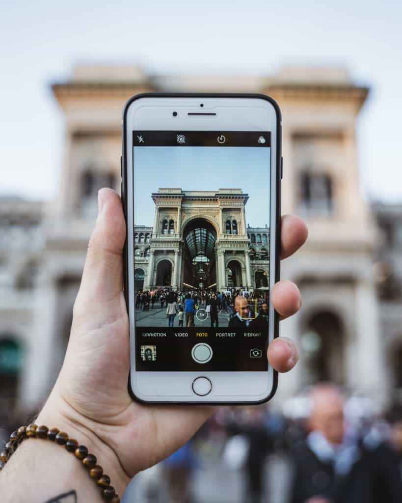 celular fotografando a entrada de em arco de um mercado antigo